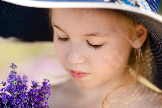 Portrair de primer plano de niña rubia en el gran sombrero y lavanda
