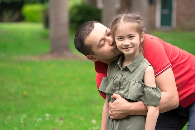 Portret del padre besando a la hija en la mejilla en el fondo de la puerta. hombre coreano besando a su hija.