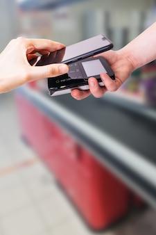Pos terminales y smartphone. al fondo hay una caja de supermercado. equipo bancario. adquisidor. aceptación de tarjetas de crédito bancarias. pago sin contacto.
