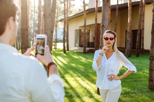 Posa para una foto. bonita mujer alegre sosteniendo su barbilla mientras tiene una mirada pensativa