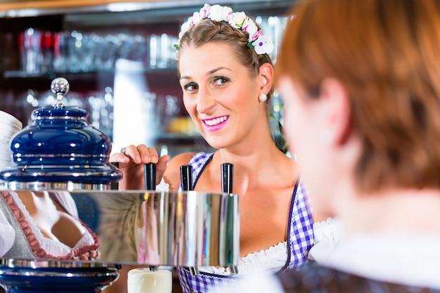 Posadero en pub bávaro con clientes.