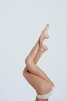 Posando para la foto. hermosas piernas femeninas delgadas levantadas.