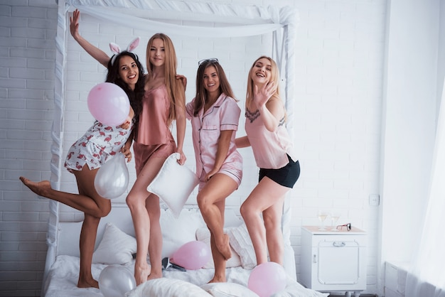 Posando para la foto. de pie en el blanco de lujo malo en vacaciones con globos y orejas de conejo. cuatro hermosas chicas en ropa de noche tienen fiesta