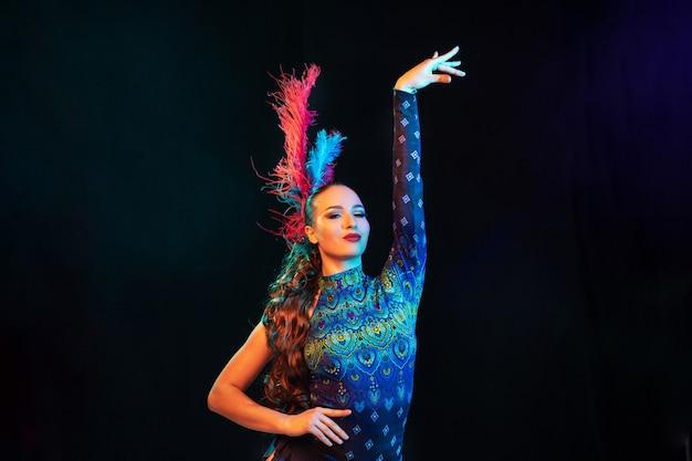 Posando. hermosa mujer joven en carnaval, elegante disfraz de mascarada con plumas en pared negra en luz de neón. copyspace para anuncio. celebración de fiestas, baile, moda. tiempo festivo, fiesta.