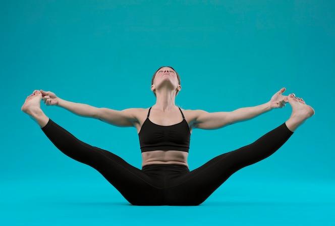 Pose de yoga mujer joven bonita