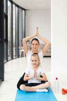 Pose de yoga con madre e hija en casa
