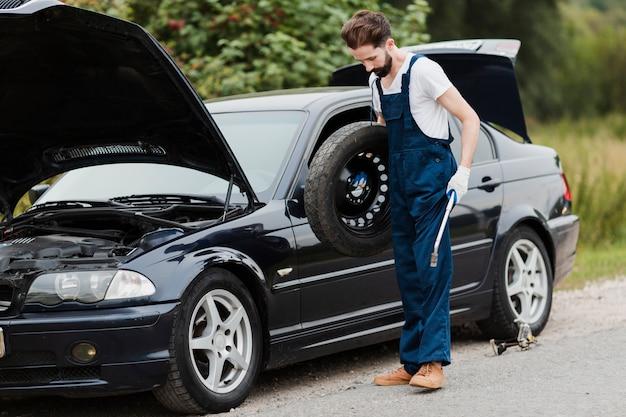 Posibilidad muy remota del hombre que sostiene el neumático de repuesto