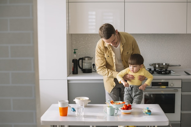 Posibilidad muy remota del padre que detiene a su hijo en la cocina