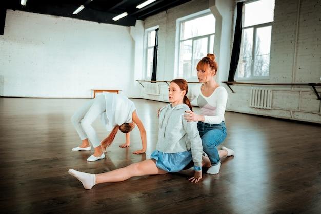 Posición del cangrejo. adolescente rubia de pelo largo vistiendo ropa deportiva blanca de pie en posición de cangrejo