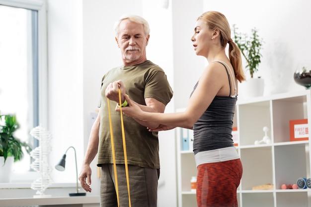 Posicion correcta. agradable mujer mayor sosteniendo la mano de un anciano mientras le muestra la posición correcta