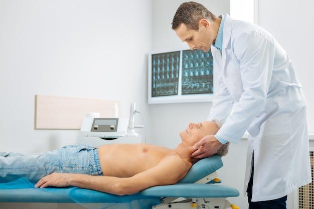 Posición correcta. buen doctor serio inteligente parado detrás de su paciente y sosteniendo su cabeza mientras lo coloca en la posición correcta