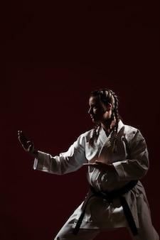 Posición de lucha de la mujer en uniforme de karate blanco