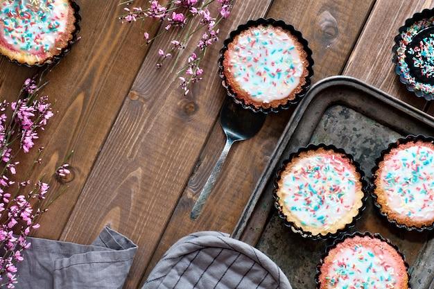 En posición plana con pequeños pasteles de loro con azúcar espolvoreado en la parte superior con pequeñas flores rosadas en una bandeja de metal para hornear y madera oscura