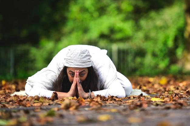 Posición de yoga entre las hojas de otoño en el parque.