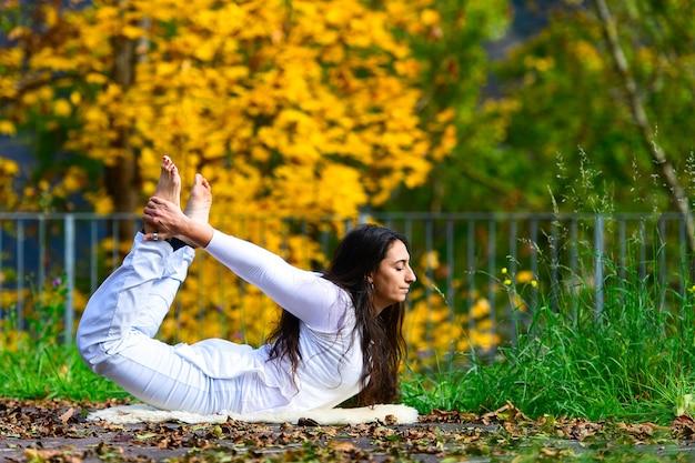 Posición de yoga por una mujer joven en el parque en otoño