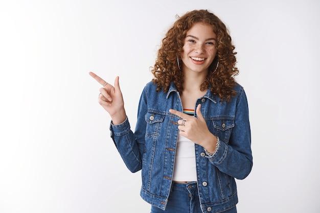 Positiva, despreocupada, amable, sonriente, pelirroja, niña, sin maquillaje, señalar hacia la izquierda, muestra, impresionante, promoción, sonriente, feliz, expresando, buen, alegre, ambiente, recomendar, skincare, producto, fondo blanco