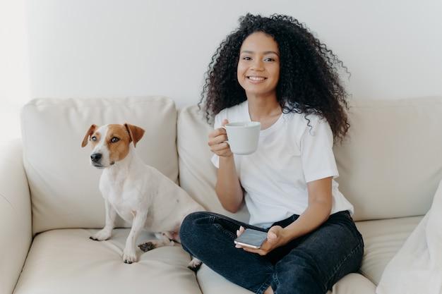 Positiva encantadora adolescente con expresión alegre, mensaje de texto en las redes sociales