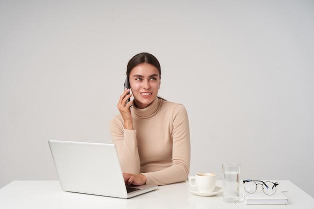 Positiva joven atractiva dama de cabello oscuro vestida con ropa formal sentada en la mesa con la computadora portátil y manteniendo la mano en el teclado, teniendo una conversación agradable por teléfono y sonriendo sinceramente