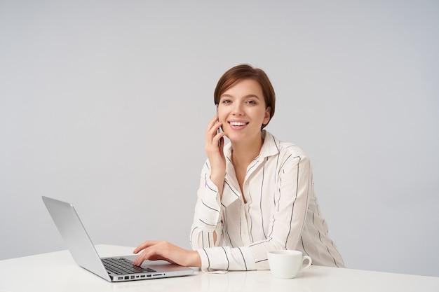 Positiva joven encantadora morena de ojos marrones mujer de negocios haciendo llamadas con su teléfono inteligente y manteniendo la mano en el teclado de la computadora portátil mientras mira alegremente