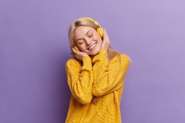 Positiva mujer europea rubia inclina la cabeza sonríe ampliamente mantiene los ojos cerrados disfruta cada pedazo de música usa auriculares inalámbricos vestida con un suéter amarillo