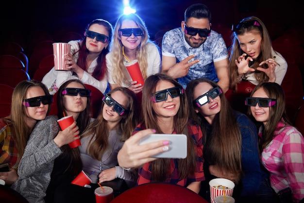 Positividad y grupo divertido de estudiantes haciendo fotos en el teléfono inteligente y tomando selfie. muchas muchachas bonitas durante la película en el pasillo del cine que toma el autorretrato que lleva en los vidrios 3d. concepto de diversión