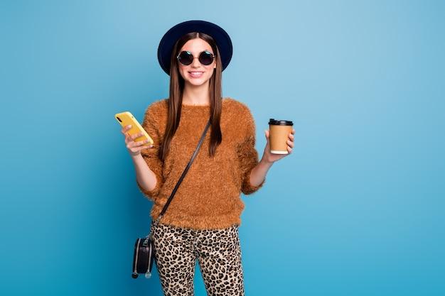 Positivo chica alegre chill usar teléfono celular blogs mantener taza bebida disfrutar primavera otoño vacaciones desgaste retro gorra marrón jumper suéter pantalones bolso negro aislado pared de color azul