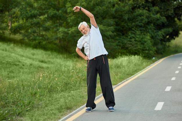 Positivo deportista senior sonriente haciendo estiramiento de la mañana.
