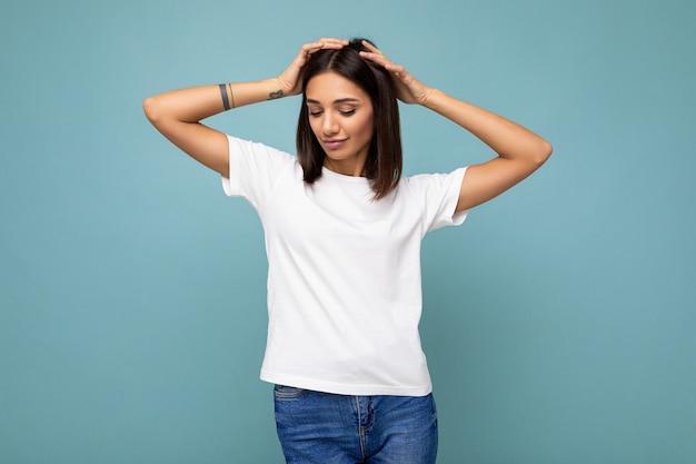Positivo feliz sexy joven hermosa mujer morena con emociones sinceras vistiendo elegante camiseta blanca para maqueta aislado