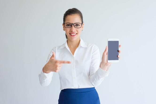 Positivo gerente mujer joven satisfecho apuntando a la pantalla del gadget.