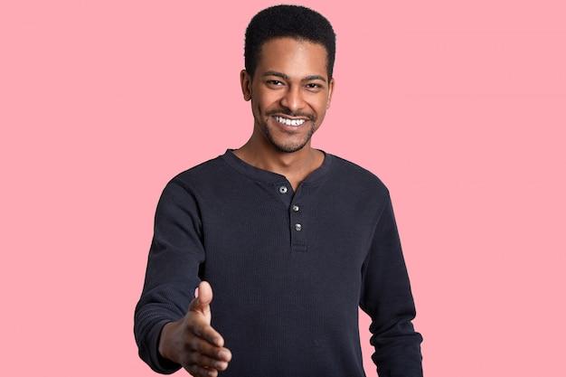 Positivo hombre negro feliz da un apretón de manos, saluda con un amigo, vestido con un jersey informal, sonríe ampliamente, tiene dientes blancos y brillantes