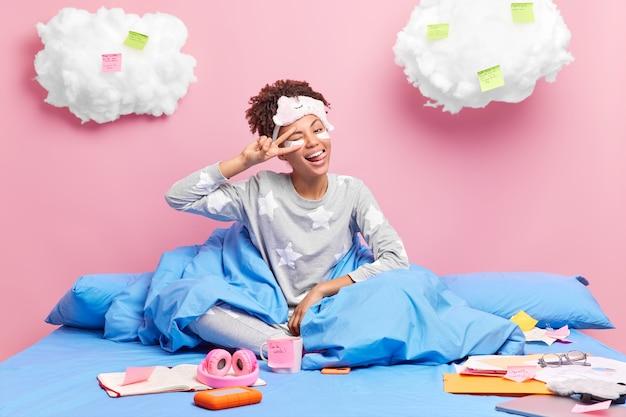 Positivo joven afroamericana hace gesto de paz saca la lengua disfruta del ambiente doméstico aprende material de casa