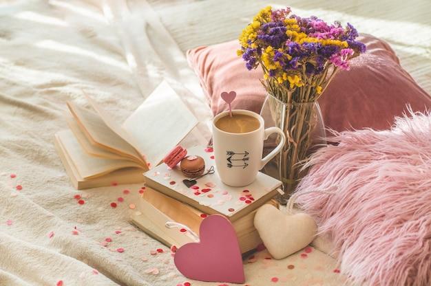 Postal feliz día de san valentín. concepto de amor para el día de la madre y el día de san valentín. corazones y libros con taza de café. tarjeta de san valentín con espacio para texto