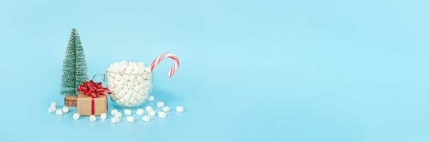 Postal de feliz navidad y próspero año nuevo. caja de regalo, árbol de navidad y taza de malvaviscos con bastón de paleta roja sobre fondo azul. concepto de vacaciones. vista frontal, espacio de copia de banner.