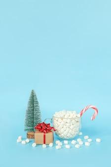 Postal de feliz navidad y próspero año nuevo. caja de regalo, árbol de navidad y taza de malvaviscos con bastón de paleta roja sobre fondo azul. concepto de vacaciones. vista frontal, espacio de copia de tarjeta de felicitación.