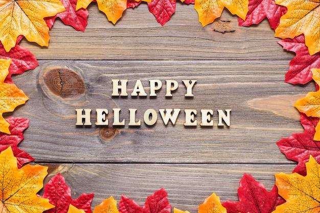 Postal de halloween. la inscripción en letras sobre una madera de hojas de arce