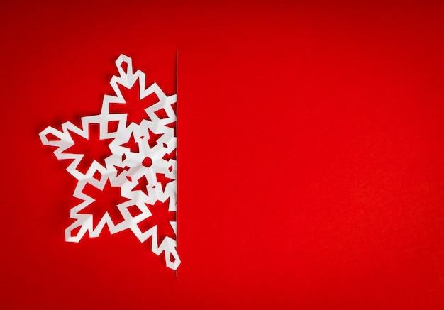 Postal de navidad de la vendimia con los copos de nieve de papel verdaderos