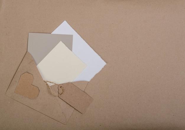 Postales blancas en un sobre marrón sobre una hoja marrón.