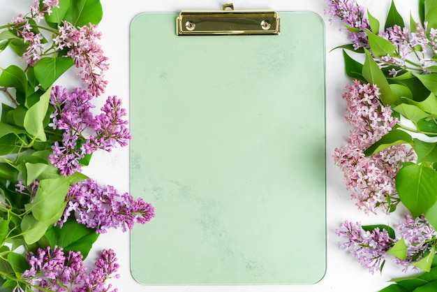 Postard del marco de flores frescas de color lilas y portapapeles para papel sobre un fondo de mármol gris claro. vista superior.