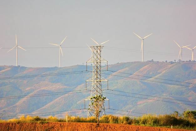 El poste de electricidad obtiene corriente eléctrica de la transferencia de la turbina eólica a su hogar, pueblo, ciudad