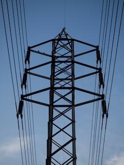 Poste eléctrico de alto voltaje de ángulo bajo con cielo azul.