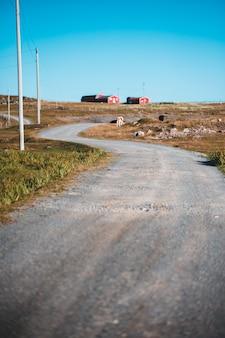 Poste de energía gris a través de casas de granero