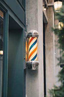 Poste de peluquero en pared gris con peluquería de madera verde
