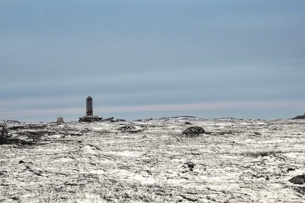 Un poste de telégrafo roto en una colina ártica cubierta de nieve