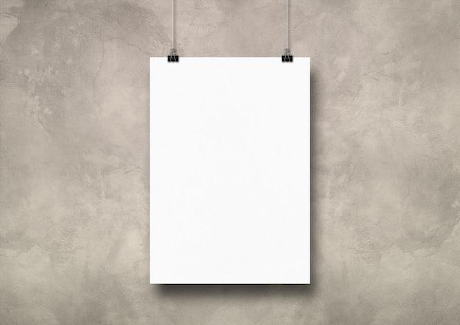 Póster blanco colgado en una pared de hormigón ligero con clips