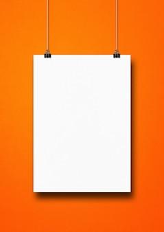 Póster blanco colgado en una pared naranja con clips.