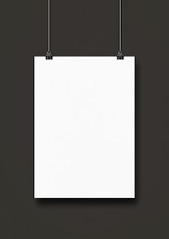 Póster blanco colgado en una pared negra con clips.