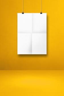 Póster blanco doblado colgado en una pared amarilla con clips. plantilla de maqueta en blanco