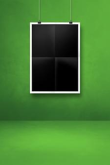 Póster negro doblado colgado en una pared verde con clips. plantilla de maqueta en blanco