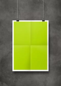 Póster plegado de color verde lima colgado en una pared de hormigón con clips