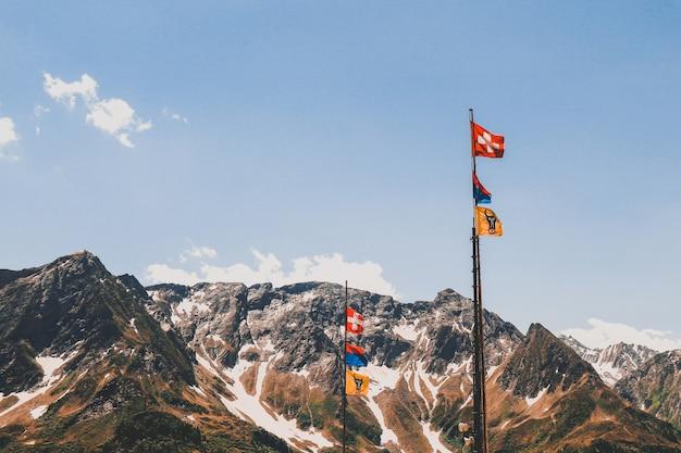Postes con banderas en las hermosas montañas rocosas cubiertas de nieve bajo el cielo nublado